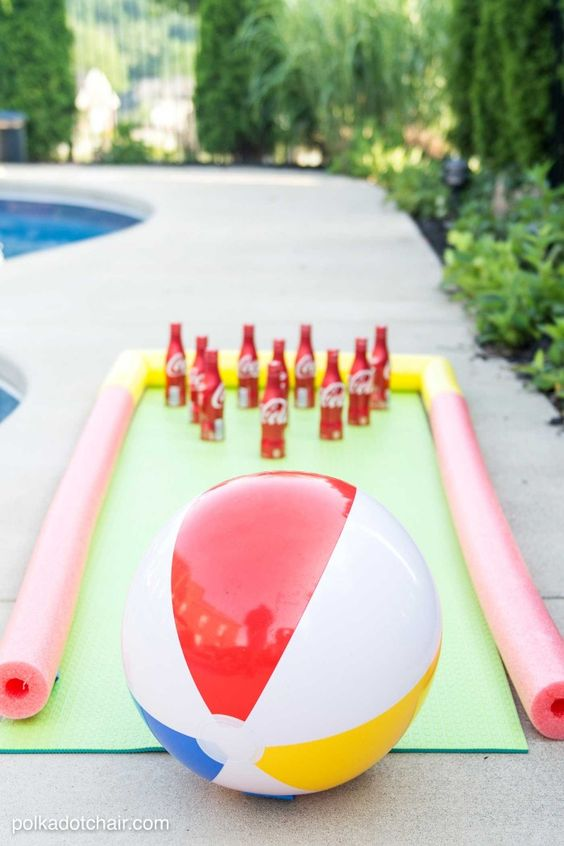 DIY Projects - Outdoor Games - DIY Bowling Game with Coke Bottles a yoga mat - pool noodle bumpers and a beach ball - fun Tutorial via The Polka Dot Chair #bowling #backyardbowling #outdoorbowling #backyardgames #diyoutdoorgames #barbecuegames #barbecueideas #backyardpartygames #partygames #outdoorgames #diygames #yardgames #diyyardgames #summergames #summerparty #party #4thofJuly #fathersday #cookoutgames