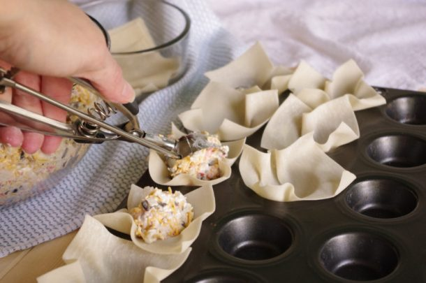 Crab and Cheddar Won Ton Purses Appetizer Easy Recipe - Scooping Filling into Won Ton Wrappers with Cookie Dough Scooper #crabandcheddarwontons #crabwontons #easyappetizers #appetizer #fingerfood #horsdoeuvres #tapas #partyfood #bitesizefood #newyearseve #tailgating #potluck #superbowl